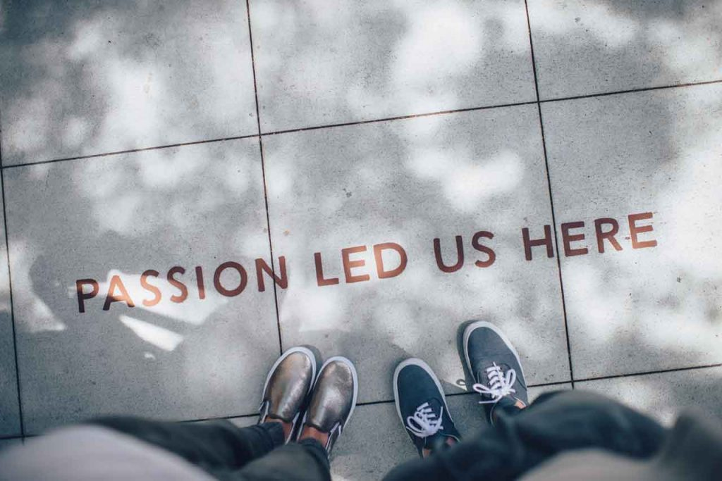 Two pairs of shoes on sidewalk with writing that reads, 'Passion Led Us Here'