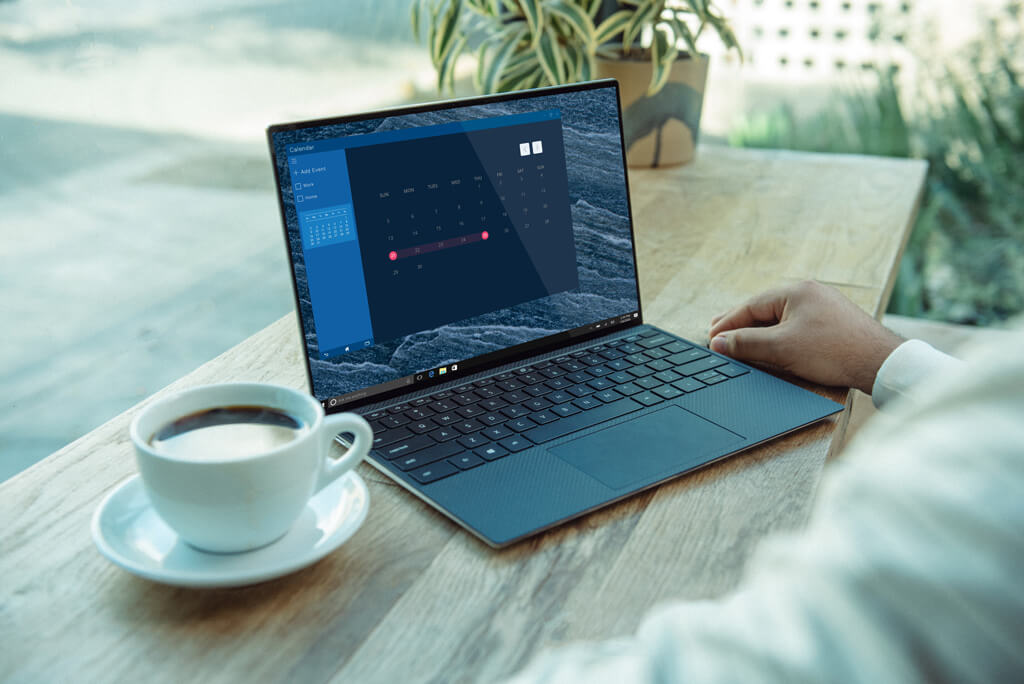 Someone sitting at laptop with cup of coffee looking at calendar on computer screen