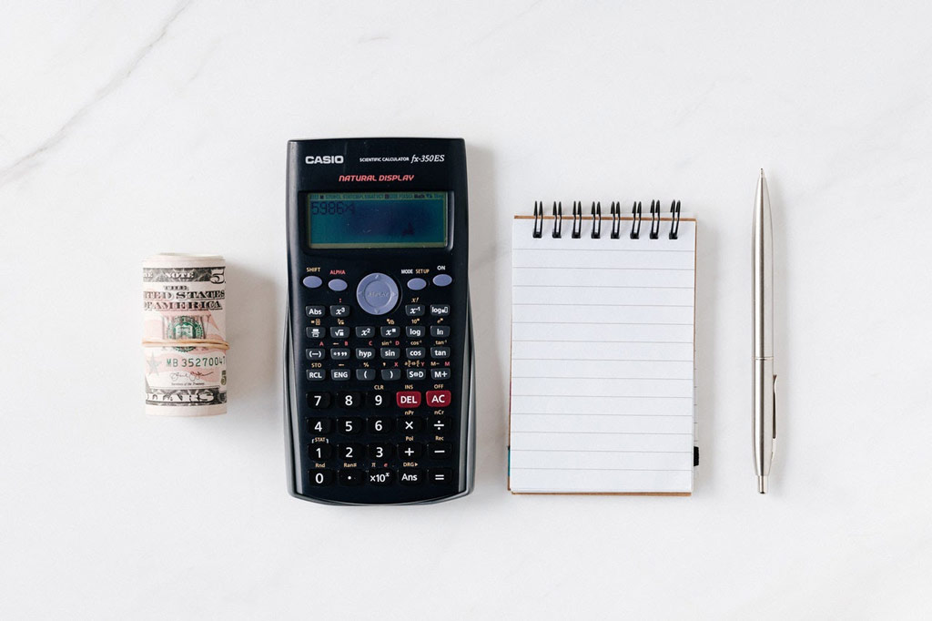 Image of calculator, notepad, and roll of cash donations from nonprofit campaigns